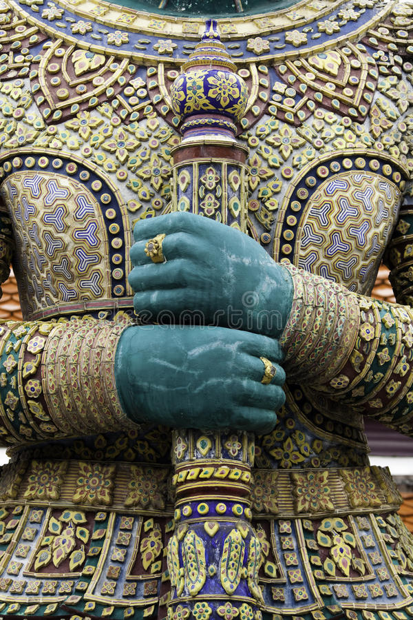 Budist Temple (detail). Detail from a budist temple in Bangkok, Thailand. Closeup of hands holding a sword royalty free stock photos