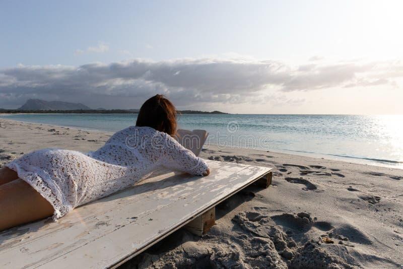 Budoni, Itália - 20 de julho de 2019: jovem mulher que encontra-se pelos olhares do mar no horizonte no alvorecer no vento vestid imagens de stock royalty free