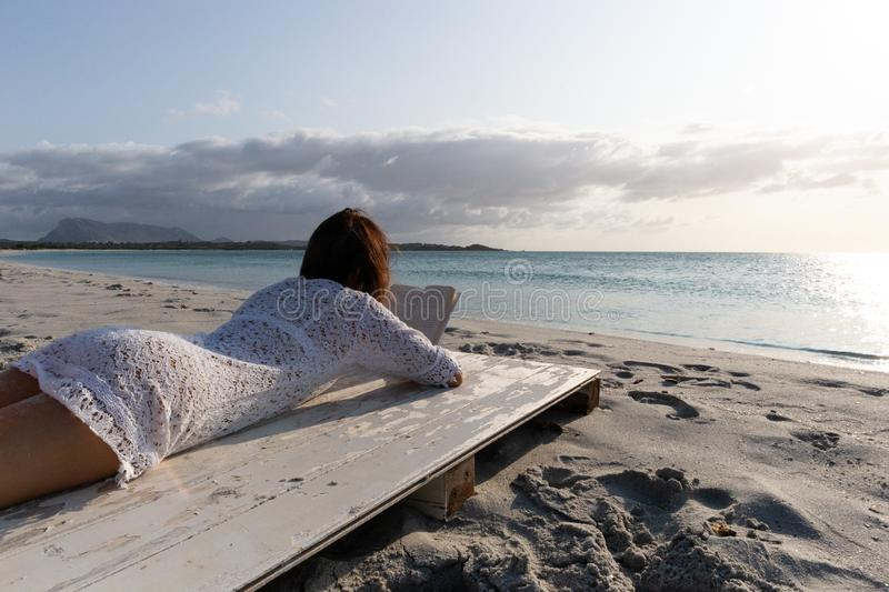 Budoni, Italy - July 20 2019: young woman lying by the sea looks at the horizon at dawn in the wind dressed in a white lace dress royalty free stock images