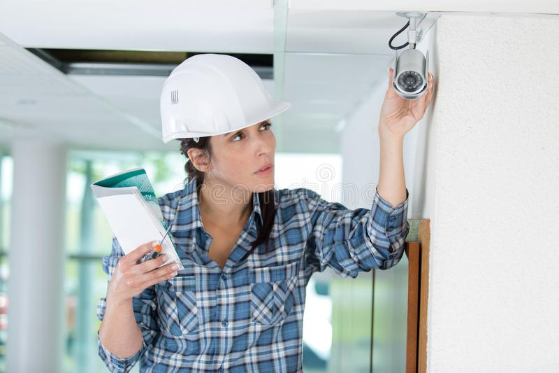Budowa żeński pracownik sprawdza cctv instalaci z drabiną obrazy stock