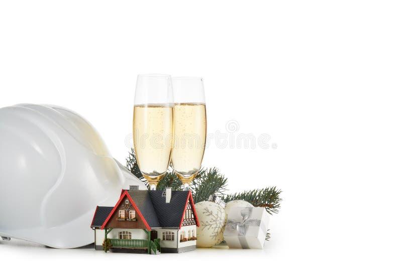 Budowa ciężki kapelusz, jedlinowe gałąź, modela dom, dwa szkła z champange i boże narodzenie ornamentem odizolowywającymi na biel fotografia royalty free