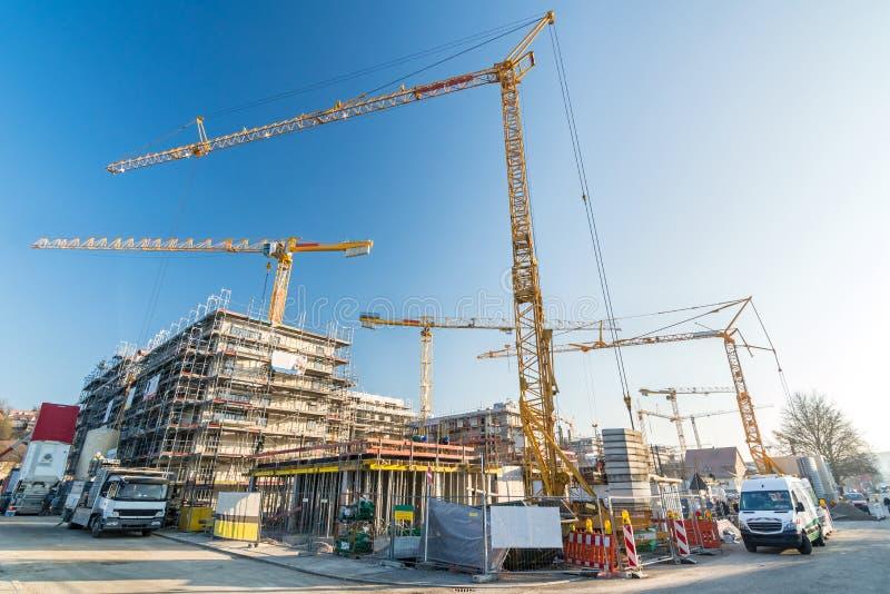 Budowa i skorupy budowa biura i budynki mieszkaniowi z wiele budowa pojazdami i żurawiami obrazy royalty free