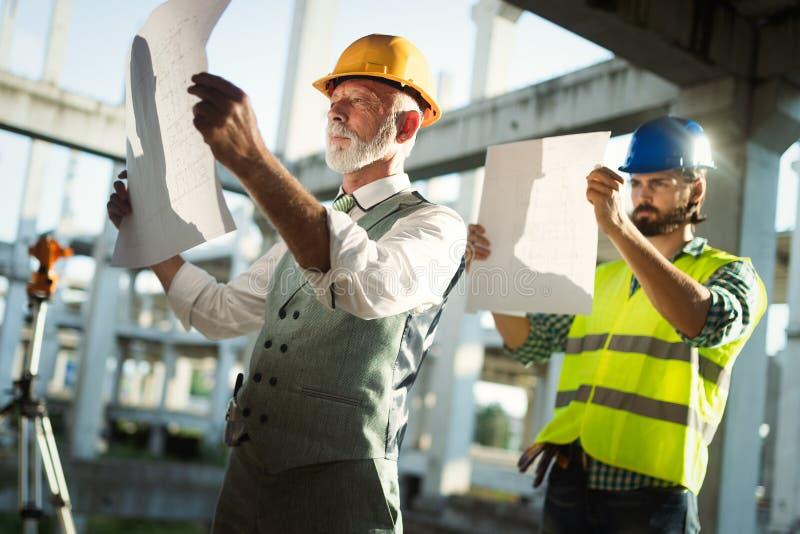 Budowa inżynierów dyskusja z architektami przy budową lub placem budowym fotografia royalty free