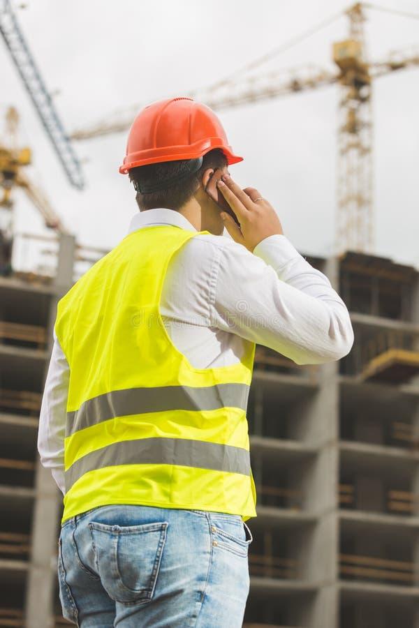 Budowa inżynier opowiada telefonem i patrzeje na budować s obrazy royalty free