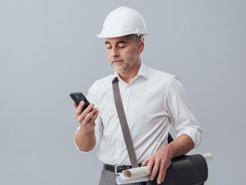 Budowa inżynier używa smartphone obraz royalty free