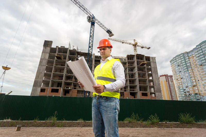 Budowa inżynier w hardhat na placu budowy z pracować c zdjęcie royalty free