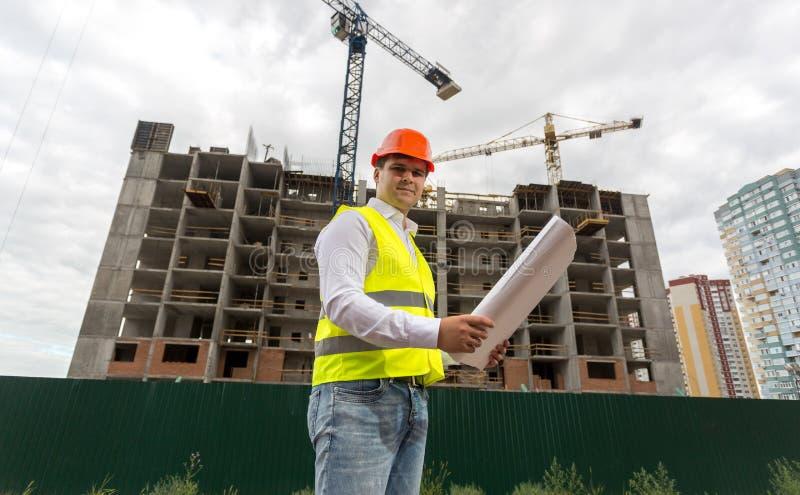 Budowa inżynier w hełmie na placu budowy przy chmurnym dniem obraz royalty free