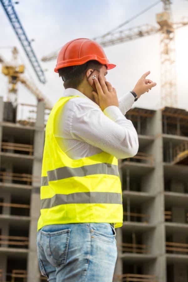 Budowa inżynier wskazuje z palcem przy budynkiem pod przeciwem obrazy royalty free