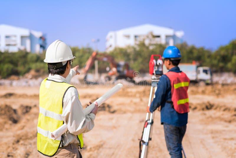 Budowa inżynier z brygadiera pracownikiem sprawdza miejsce obraz royalty free