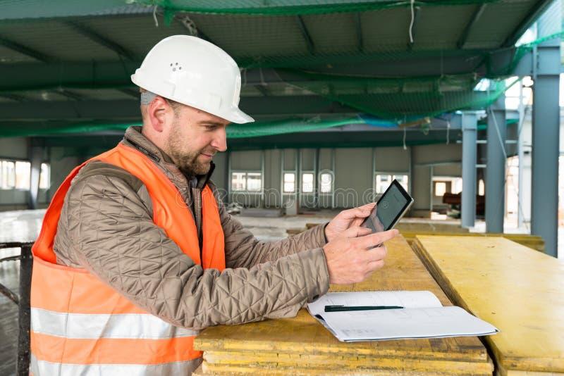 Budowa nadzorca z cyfrową pastylką na miejscu zdjęcie royalty free