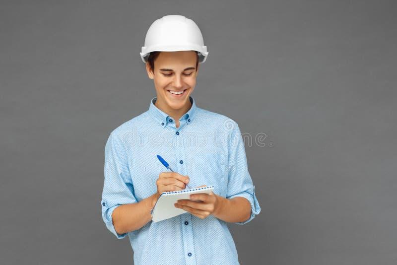 Budowa Nastolatek chłopiec w ciężkiego kapeluszu pozycji na popielatych bierze notatkach w notatniku rozochoconym fotografia royalty free