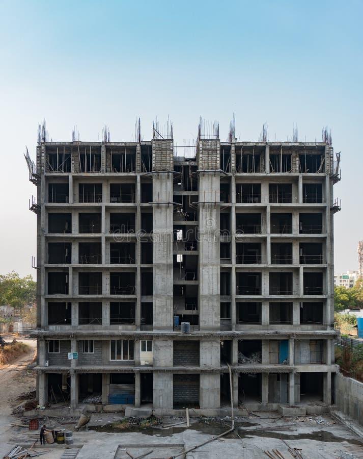 Budowa nowożytny wysoki budynek mieszkalny z pracownikami pracuje w bloku mieszkaniowym z stalowymi prąciami rozpraszającymi fotografia stock