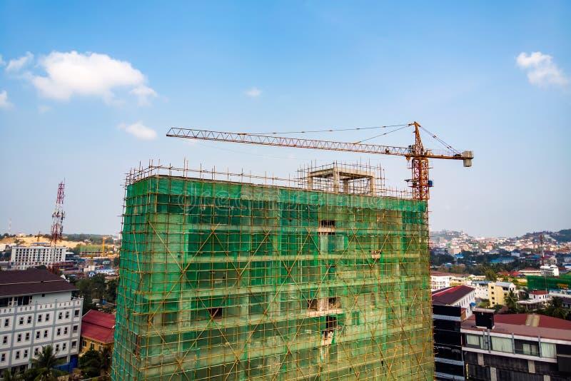 Budowa obok nowożytnego biura, budynek mieszkalny Pracujący żuraw i siatka zabezpieczająca z obłocznym niebieskim niebem zielone  obraz royalty free