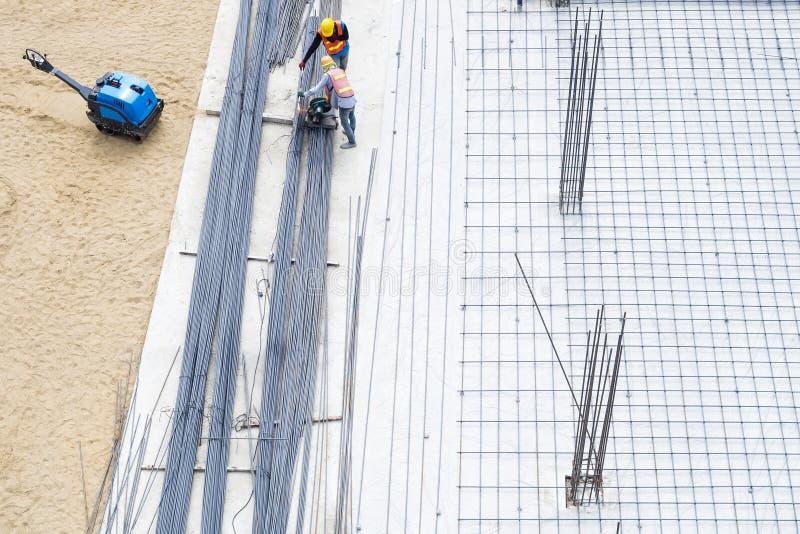 Budowa pracownicy na cementowych podłogowych Stalowych Prąciach Opierają się budynek obrazy stock