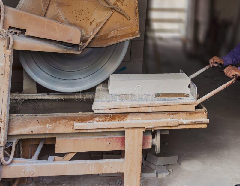 Budowa: Pracownik z maszynowego rozcięcia blokami fotografia royalty free