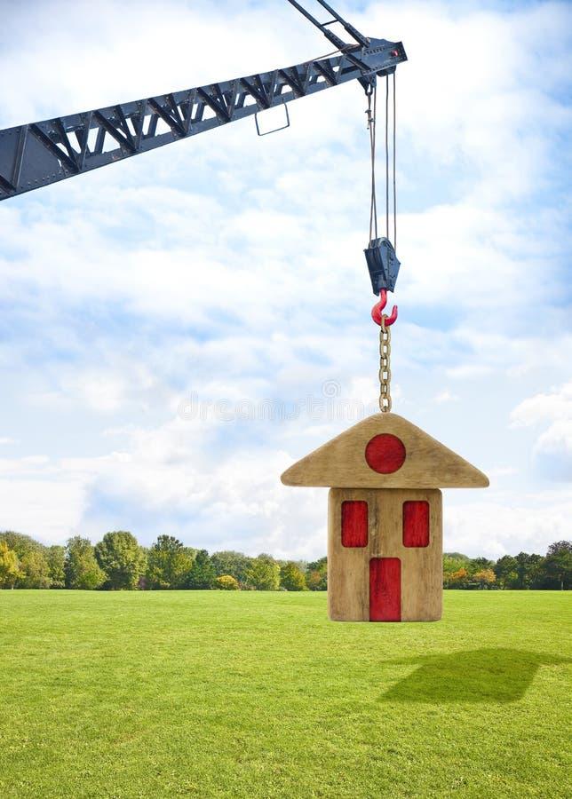 Budowa prefabrykacyjny budynek - pojęcie wizerunek z basztowym żurawiem trzyma drewnianego dom ilustracji