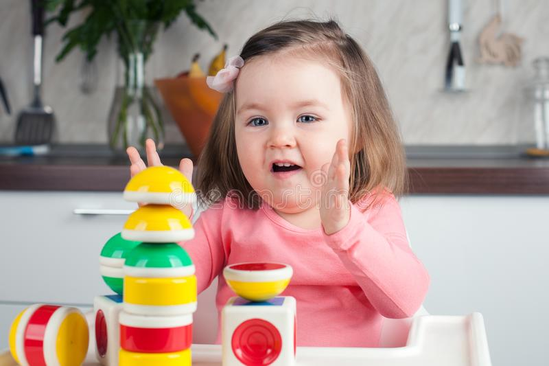 Budowa 2 roczniaka dziewczyna z d?ugie w?osy sztukami z projektantem w domu, budowy g?ruje, raduje si? przy sukcesami, fotografia royalty free