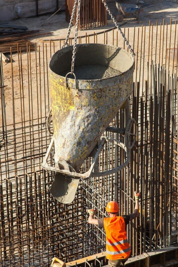 Budowa wielki handlowy budynek Pracowników wp8lywy cement dla nalewać wzmacnienie przy budową zdjęcia stock