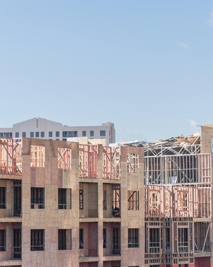 Budowa z żurawia, garażu i kompleks apartamentów jasnym niebieskim niebem, zdjęcia stock