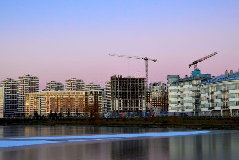 Budowa z budowa żurawiami i wysokimi domami na tle wieczór zmierzch zamarznięty jezioro i zimno fotografia royalty free