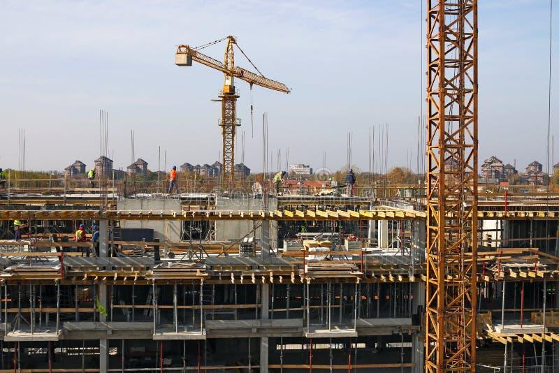 Budowa z pracownikami i żurawia przemysłem zdjęcia stock