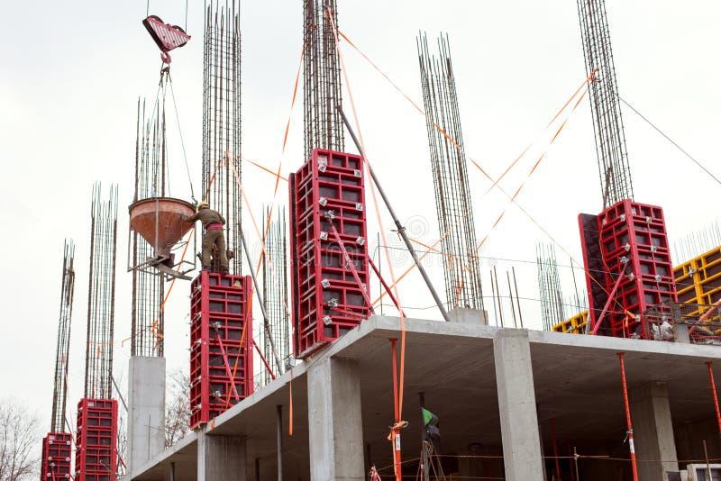 Budowa zbrojony betonowy drapacz chmur, pracownicy i żuraw, Pojęcie święto pracy zdjęcia stock