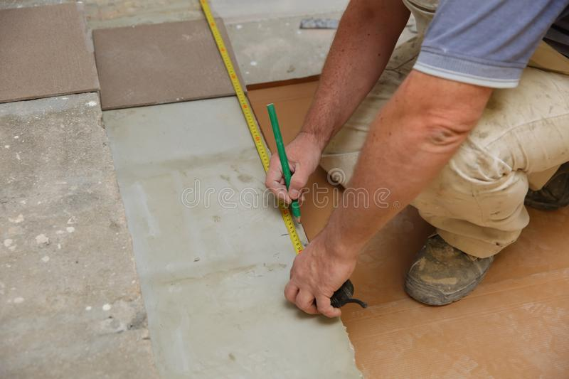 The builder measures the floor with a scoop to arrange the laying of ceramic tiles on the stairs well. Budowlaniec measures and plans to lay ceramic tiles stock images