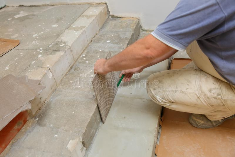 The builder measures the floor with a scoop to arrange the laying of ceramic tiles on the stairs well. Budowlaniec measures and plans to lay ceramic tiles stock photo