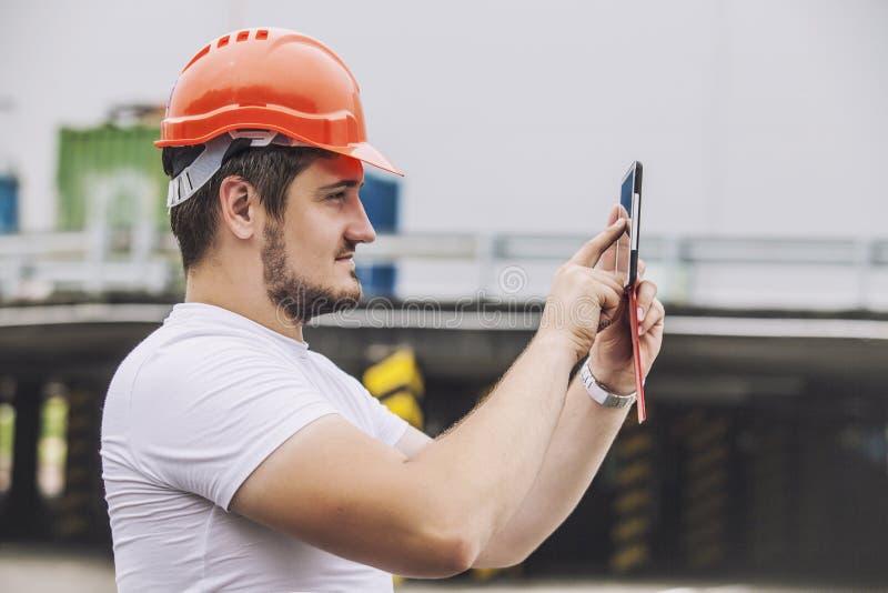 Budowniczego mężczyzna pracuje z pastylką w ochronnym hełmie obraz stock