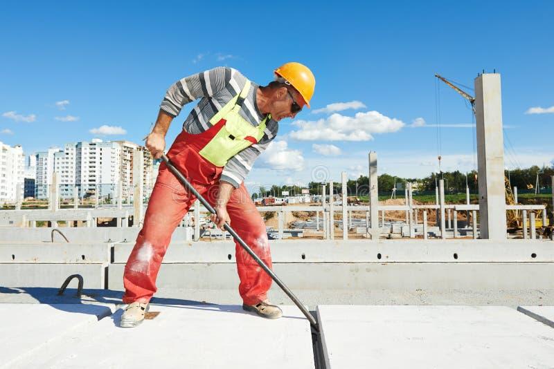 Budowniczego pracownik instaluje betonową płytę obraz stock