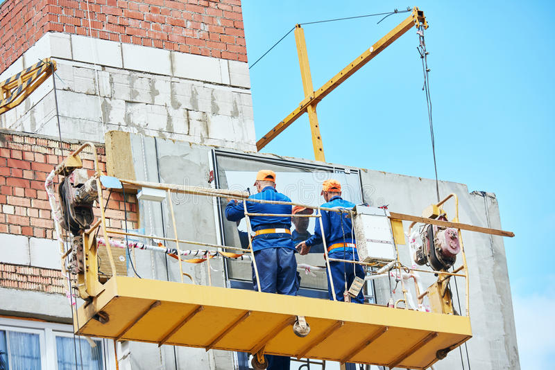 Budowniczego pracownik instaluje szklanych okno na fasadzie obraz stock