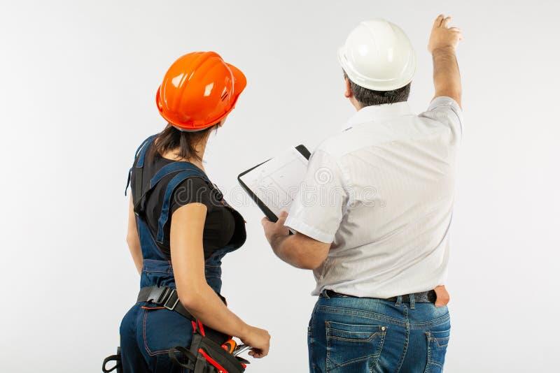 Budowniczowie dyskutuje projekty z pastylką w hardhat lub hełmie fotografia stock
