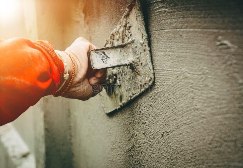 Budowniczowie gipsują ściany dom z akuratnością obrazy royalty free