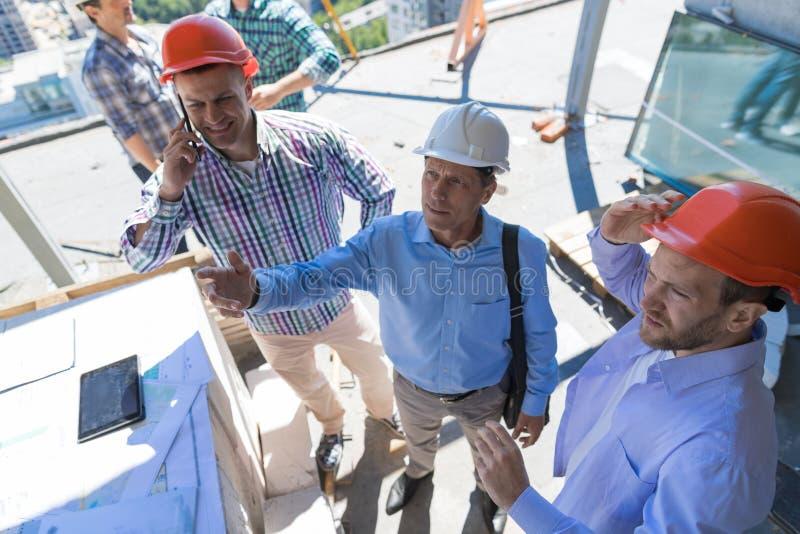 Budowniczowie Na budowie Z kontrahentem Przegląda Buiding projekt, Drużynowy spotkanie Z architekta Biznesowym mężczyzna obrazy stock