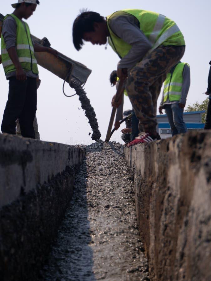 Budowniczowie nalewa cement podczas ulepszenia mieszkaniowa ulica obrazy royalty free