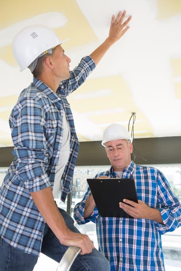 Budowniczy i architekt sprawdza budowa niedokończonego dom obrazy stock