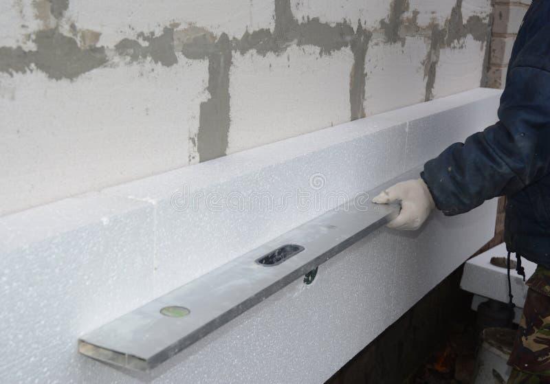 Budowniczy instaluje styrofoam izolacji deskę i mierzyć z spirytusowym poziomem Powierzchowności Piankowa izolacja zdjęcia stock