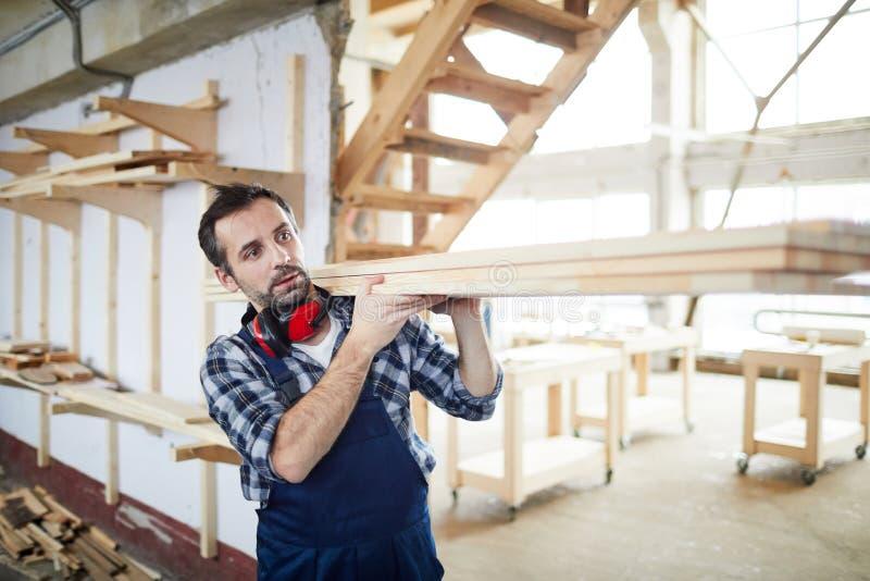 Budowniczy niesie drewniane deski zdjęcia stock