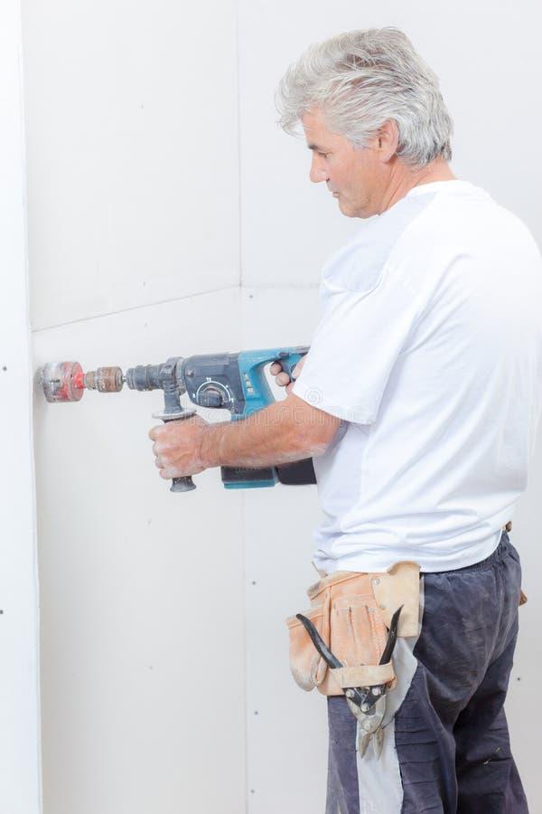 Budowniczy używa świder z doczepianiem robić dziury obraz stock