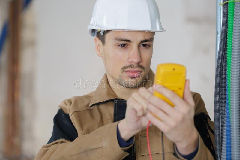 Budowniczy używa cyfrowego multimeter odizolowywającego zdjęcia stock