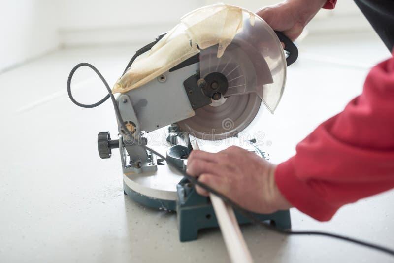 Budowniczy używa małą elektryczną kurendę zobaczył ciąć długość p fotografia royalty free