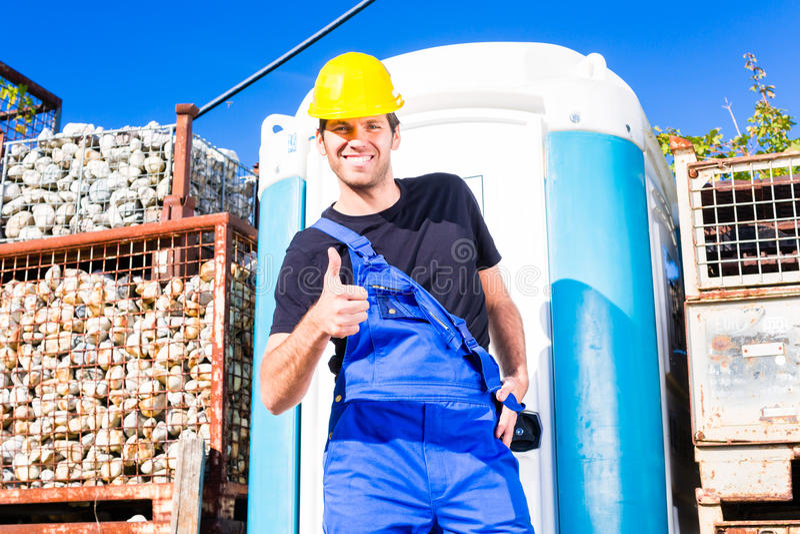 Budowniczy używa mobilną toaletę na miejscu zdjęcie stock