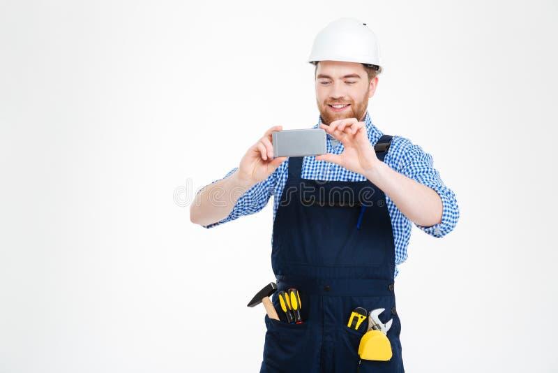Budowniczy w hełmie bierze fotografie używać smartphone fotografia stock