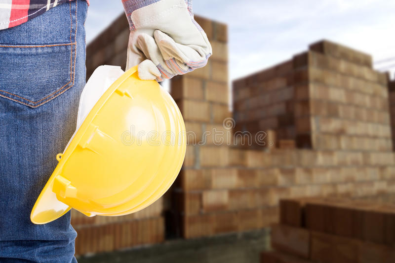 Budowniczy z żółtym hełmem i pracującymi rękawiczkami obraz royalty free