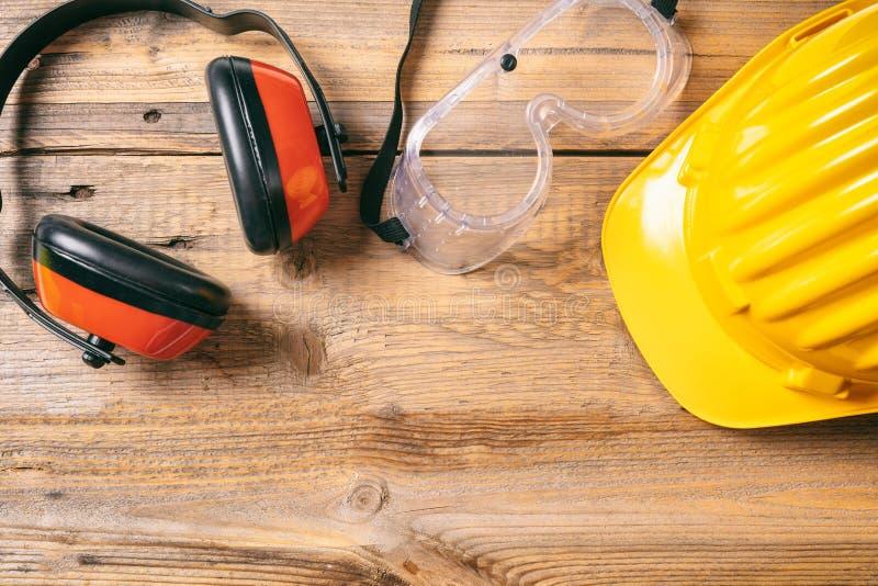 Budowy bezpieczeństwo Ochronny ciężki kapelusz, hełmofony i szkła na drewnianym tle, kopii przestrzeń, odgórny widok fotografia stock