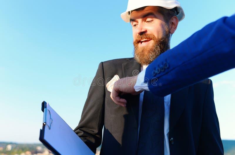 Budowy i łapówkarstwa pojęcie Ręka stawia pieniądze w coworkers kieszeń obrazy royalty free