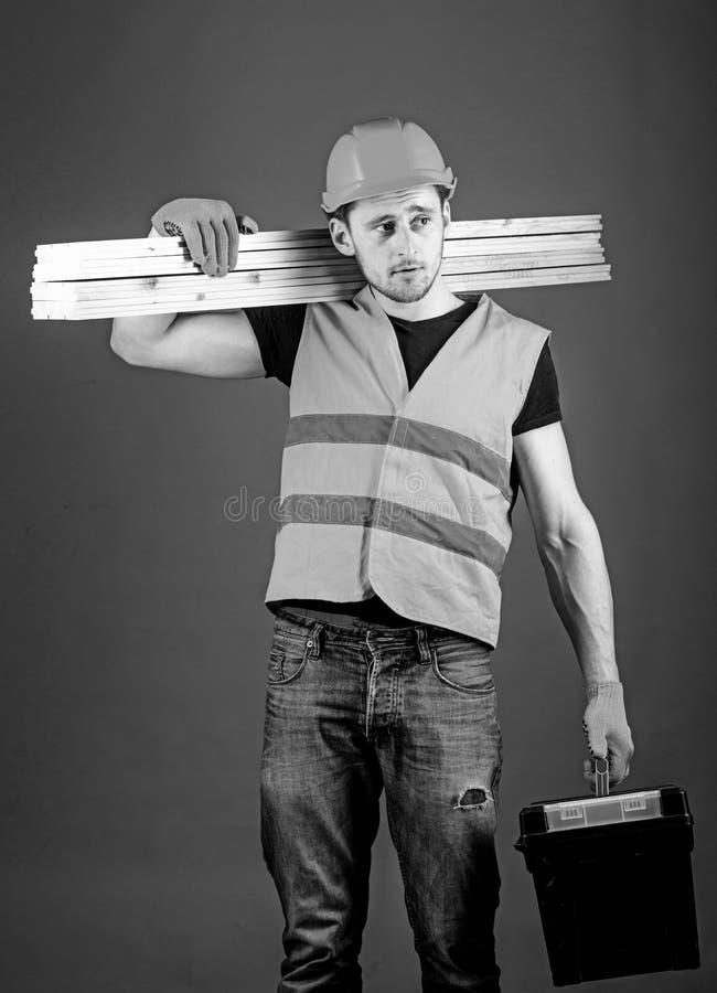 Budowy i woodworking pojęcie Cieśla, woodworker, robotnik, budowniczy na marzycielskiej twarzy niesie drewnianych promienie dalej obrazy stock