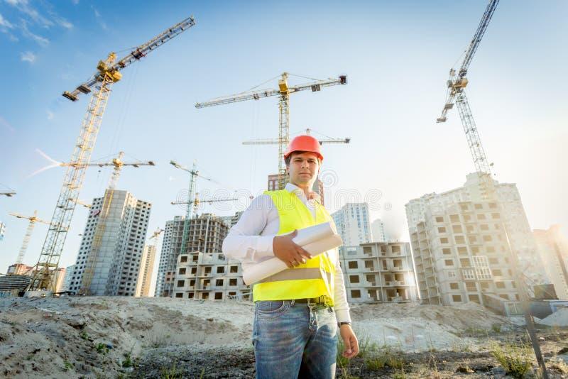Budowy inspektorski pozować z projektami na placu budowy zdjęcia royalty free