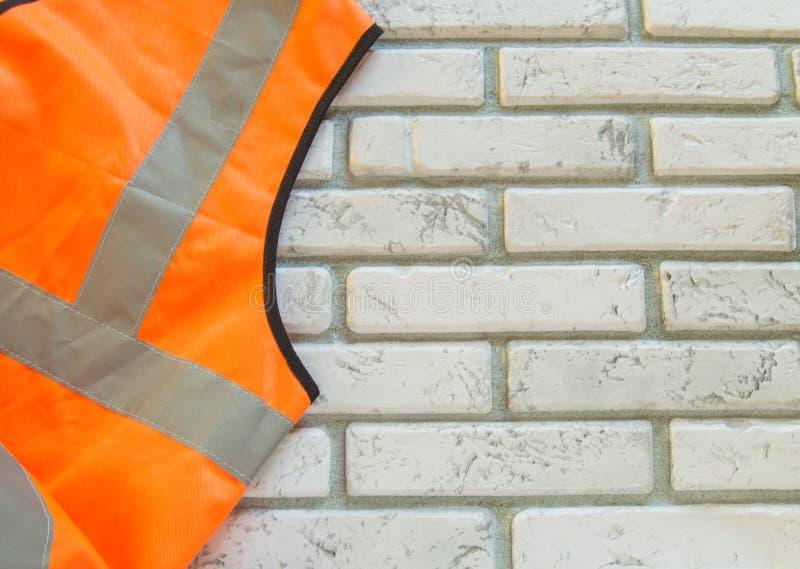 Budowy pomarańczowa kamizelka z odbijającymi lampasami dla bezpieczeństwa na białym ceglanym tle, kopii przestrzeń zdjęcie stock