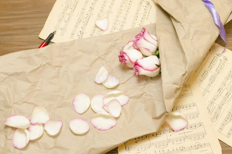 Buds and rose petals in wrapping paper lie on the pages with musical notes royalty free stock photo